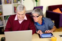 Happy elder couple writing email to grandsonElder woman looking email that husband is writing with computer at home